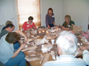 Spiritual retreat participants sculpting themselves in clay