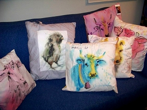 Painted and printed pillows on blue sofa