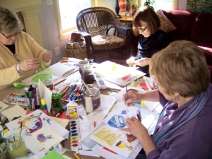 Journal makers working at table filled with art supplies