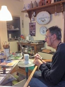 Artisan painting a ceramic piece