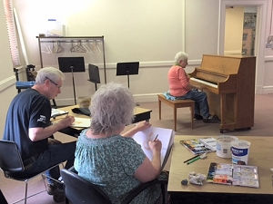 Dorothy plays piano while modeling for watercolor class at The Center