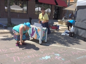Jo chalks a thank-you to Iowa City residents during 2016 Iowa Arts Festival