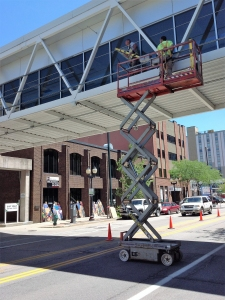 Workers use a lift to install artwork outside the Cedar Rapids skywalk
