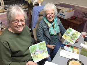 Judy Coverdale and Jo Myers-Walker with their watercolor paintings at the Coverdales' farm home
