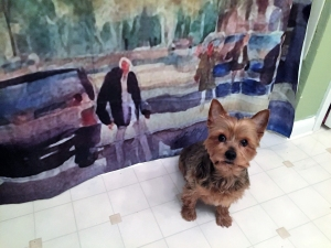 Cute little dog next to shower curtain digitally printed with watercolor street scene by Jo Myers-Walker