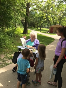 Fellow path pedestrians watch Jo Myers-Walker sketching in Iowa City