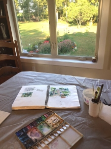Sketchbook on table with view of farm home's yard through a window