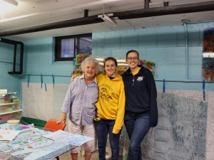 Jo, Whitney, and Grace shown collaborating on the mural for Mercer Park Aquatic Center in Iowa City