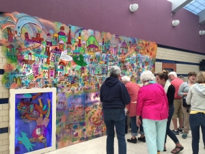 People at ribbon cutting for the new mural at Mercer Park Aquatic Center in Iowa City