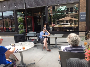 An artist's model poses at a coffee shop sidewalk table while being sketched by class members in downtown Iowa City