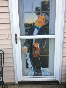 Foamcore cutout of teacher holding violin by Jo Myers-Walker, posed inside screen door