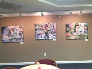 Three stretched fabric prints digitally printed with watercolor images by artist Jo Myers-Walker shown displayed side-by-side on a wall