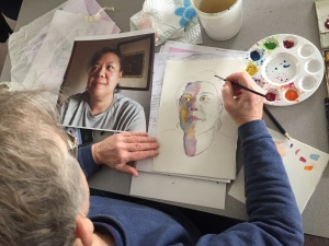 View over the shoulder of an artist creating a watercolor portrait based on a photograph