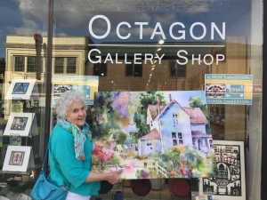 Artist Jo Myers-Walker poses in front of the Octagon Gallery Shop in Ames, Iowa with fabric print of one of her watercolor paintings