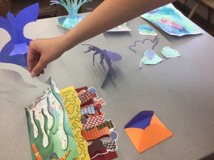 A workshop participant selects colorful paper shapes to add to a three-dimensional artwork