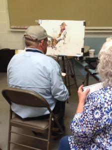 Artist Charles Reid paints a cowboy figure at an easel during a 2015 workshop