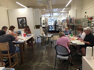 Painters work at tables in a watercolor workshop at Artisan Gallery 218 in West Des Moines, Iowa