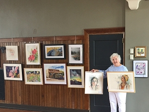 Jo Myers-Walker poses with paintings to add to the IWS 2019  Annual Exhibition at La Poste in Perry, Iowa
