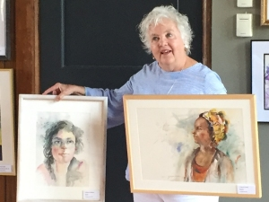 Jo Myers-Walker with two of her paintings, watercolor portraits of women, accepted into the IWS 2019 Annual Exhibition