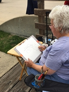 Jo Myers-Walker sketching in Amana, Iowa during the 2019 Catiri's Fresh Paint event