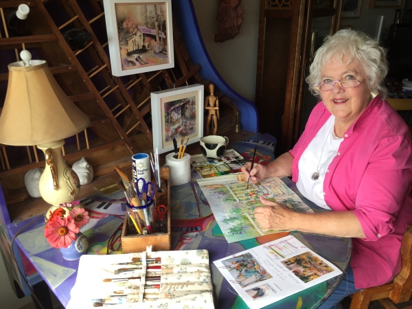 Portrait of artist Jo Myers-Walker painting at a desk made from an upright piano and surrounded by painting supplies
