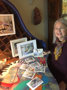 Michaela poses with watercolor card set arranged on piano table