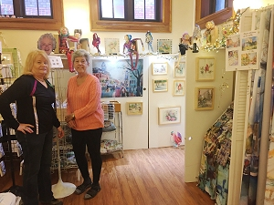 Friends Jeanette and Joan help set up Jo Myers-Walker's booth at the 2019 Eastside Artists Show and Sale in Iowa City
