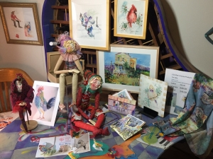 Watercolor paintings, cloth figures, notecards, and other projects by artist Jo Myers-Walker displayed on a desk