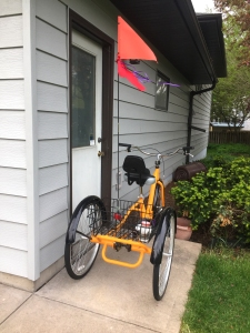 Yellow three-wheeled bicycle with bright orange flag