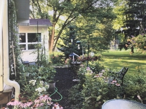 Photo of a backyard garden in summer with flowers and patio chairs