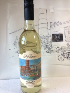 Bottle of 2020 Oktoberfest white wine from Ackerman Winery in front of sketch for the label art by Jo Myers-Walker