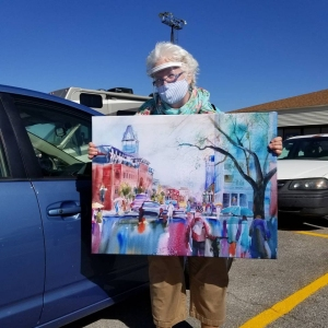 Artist Jo Myers-Walker holding a fabric print of her watercolor painting of a rainy day in downtown Iowa City