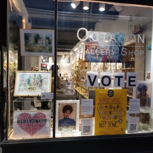 Storefront of the Octagon Shop with artwork and signs supporting Black Lives Matter and voting rights