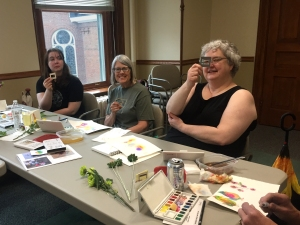Members of a watercolor workshop at a table with watercolor supplies
