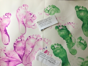 Multiple left and right footprints in purple and green paint respectively on a large sheet of white paper