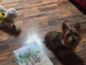 Two small dogs next to a small watercolor illustration by artist Jo Myers-Walker