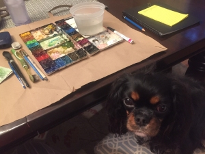 A small Cavalier King Charles Spaniel dog sits on a chair in front of a watercolor workstation